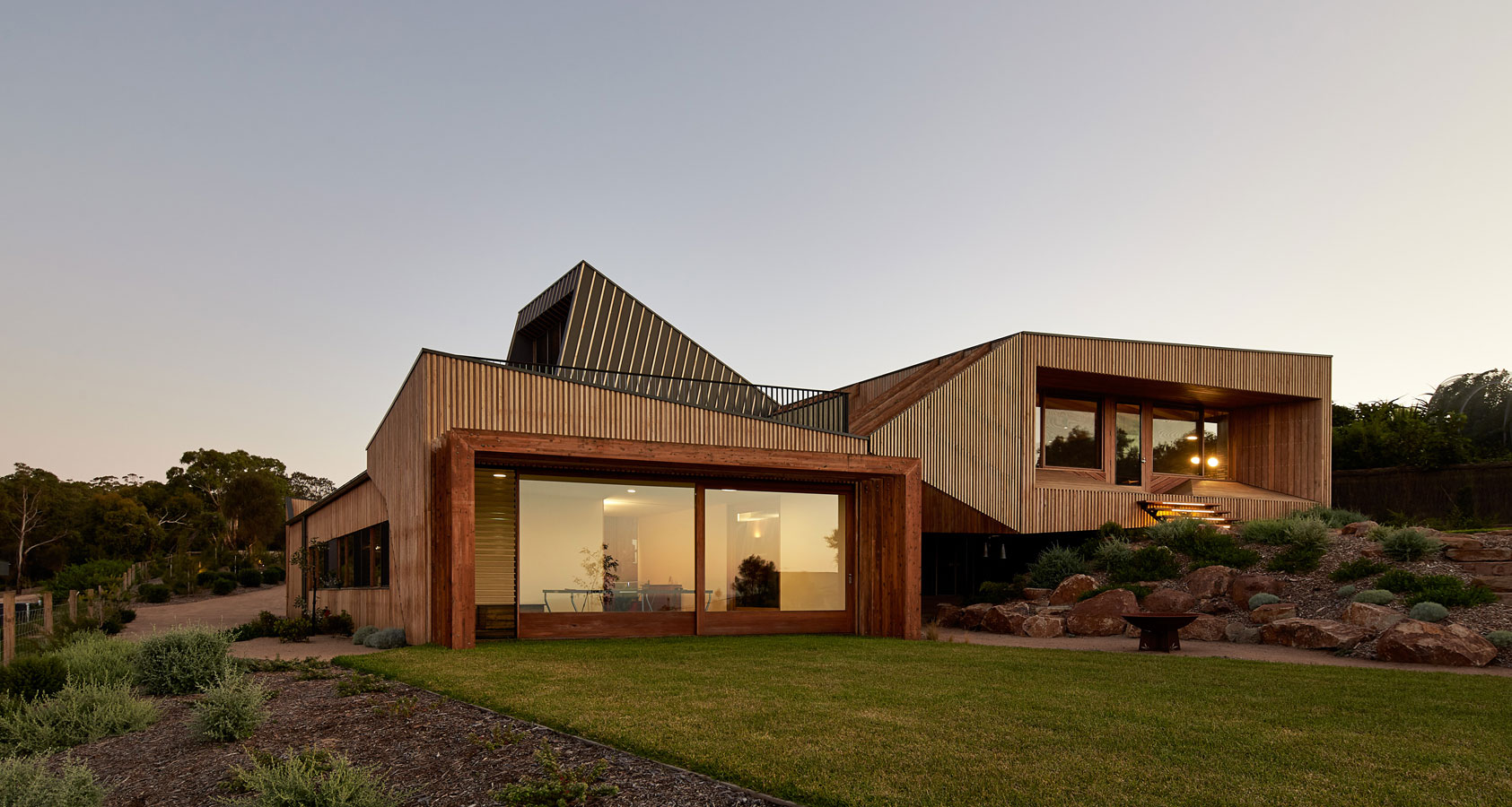 Overend Constructions, Split House, full exterior view at dusk, glass sliding doors, timber cladding, landscaped garden, BKK Architects