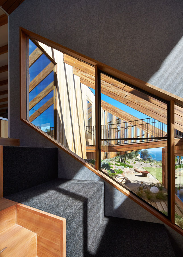 Overend Constructions, Split House view from interior stairs through window to outdoor timber structure and elevated path, BKK Architects